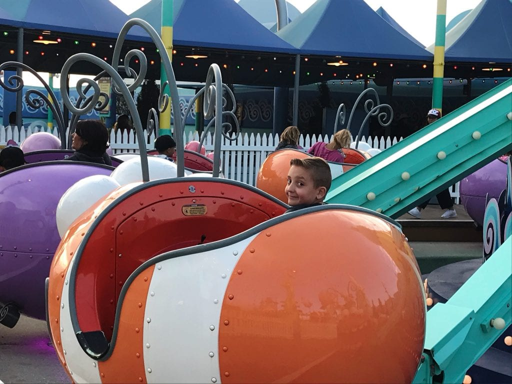 A boy riding in a large orange bug at Universal Studios Hollywood.