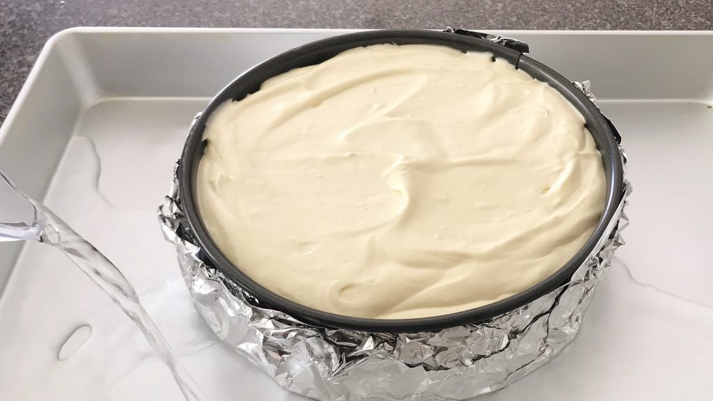 Cheesecake batter in a springform pan, placed in a roasting pan being filled with water.