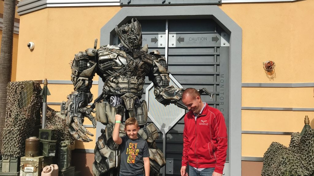 A large Transformer suit with a man and a child.