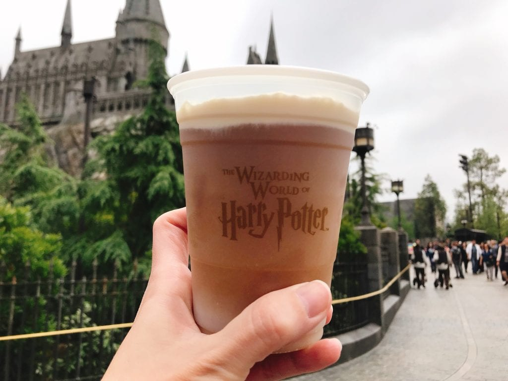A cup of Frozen Butterbeer in front of Hogwarts Castle at the Wizarding World of Harry Potter at Universal Studios Hollywood.