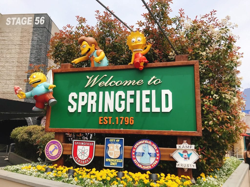 "A sign with characters from The Simpsons that says, ""Welcome to Springfield"""