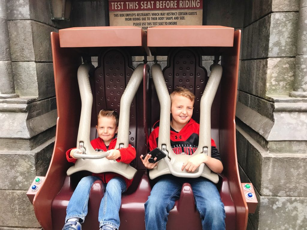 "Two kids sitting in roller coaster seats at the entrance of ""Harry Potter and the Forbidden Journey"" in the Wizarding World of Harry Potter inside Universal Studios Hollywood."