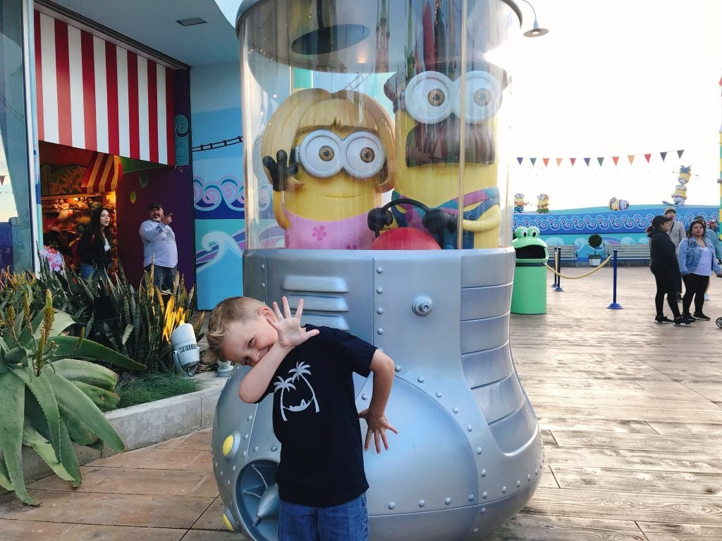 A child posing in front of Minions from the Despicable Me movies at Universal Studios Hollywood.