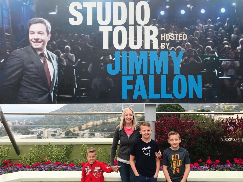 "A family with a sign of Jimmy Fallon that says ""Studio Tour Hosted By Jimmy Fallon"""