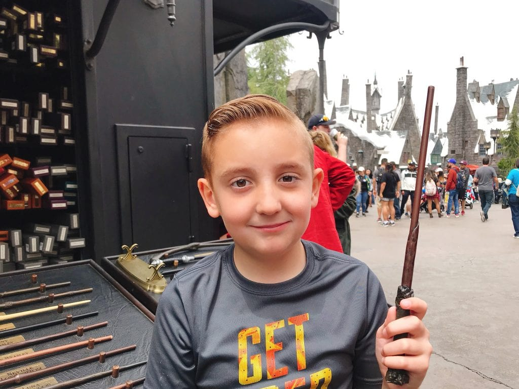 A boy holding a magic wand at The Wizarding World of Harry Potter inside Universal Studios Hollywood.