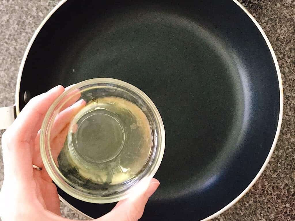 A bowl of vegetable oil to be added to a saucepan.