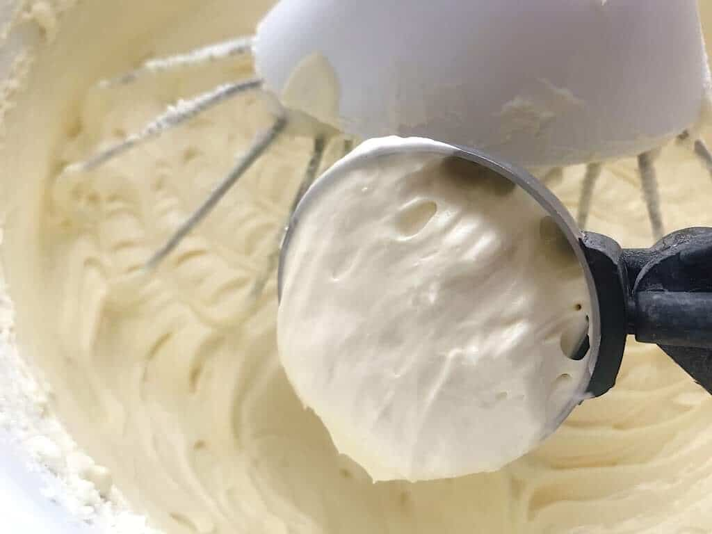 A scoop of cheesecake batter over a mixing bowl of batter.