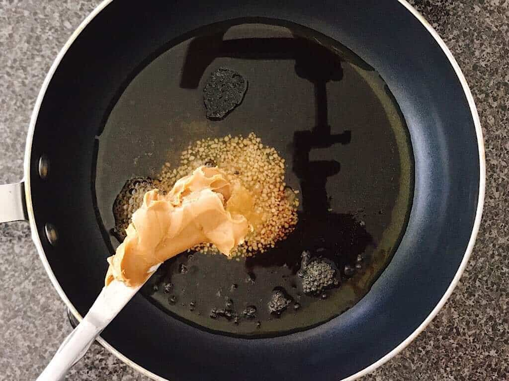 A knife with peanut butter held over a saucepan to make Spicy Thai Noodles with Chicken.