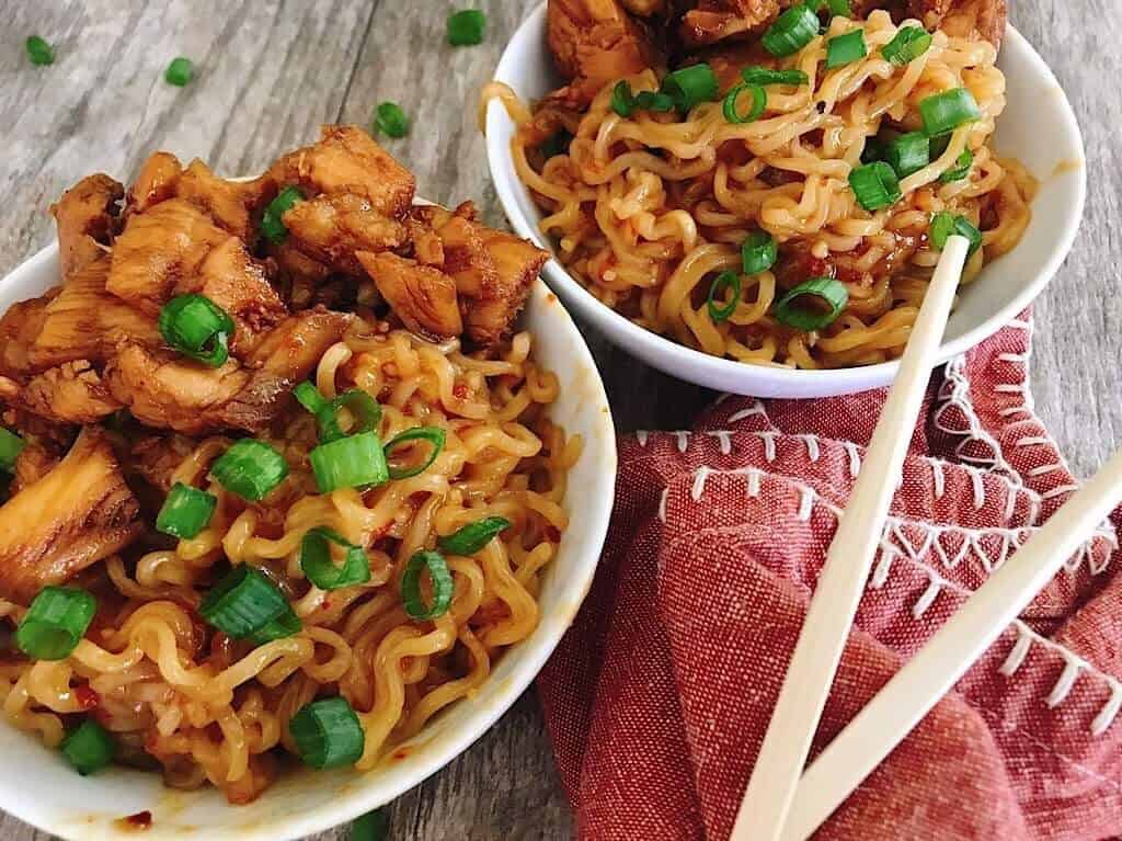 Two bowls of noodles with chicken and chopsticks.