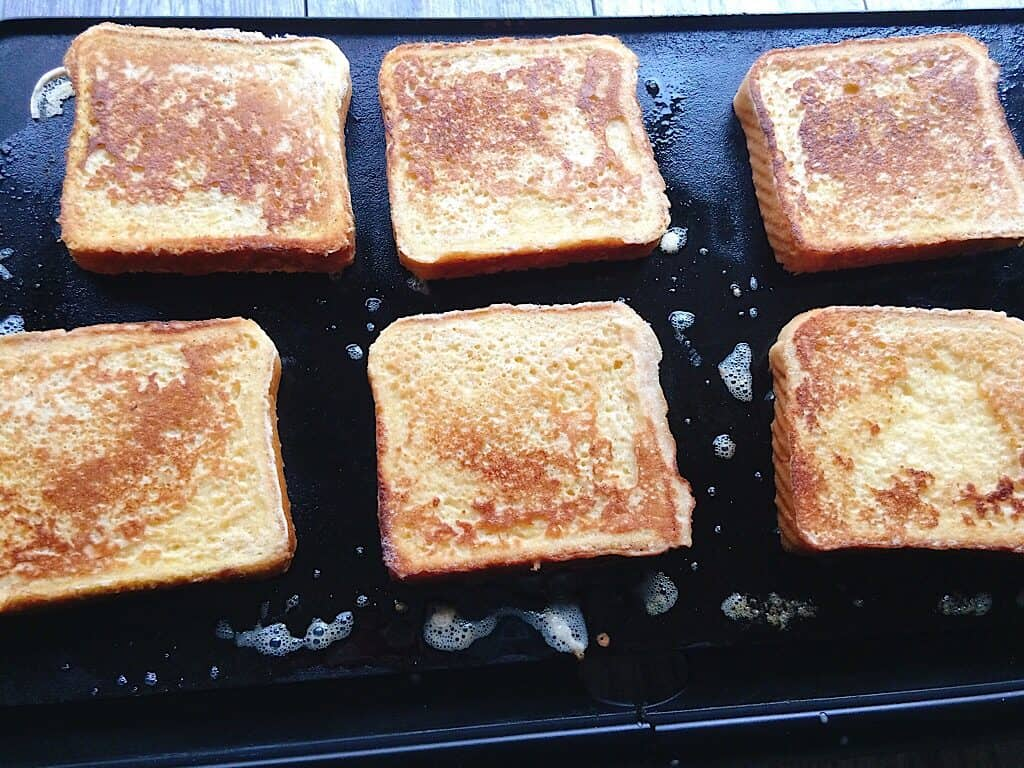 Slices of French Toast on a grill.