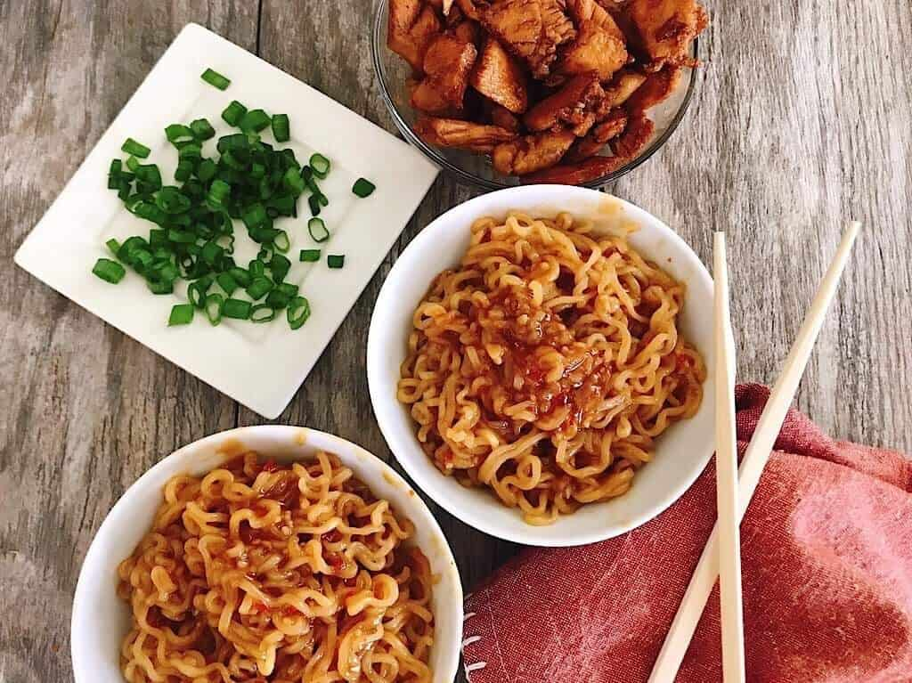 Two bowls of Spicy Thai Noodles with chicken, chopped green onions, and chopsticks.