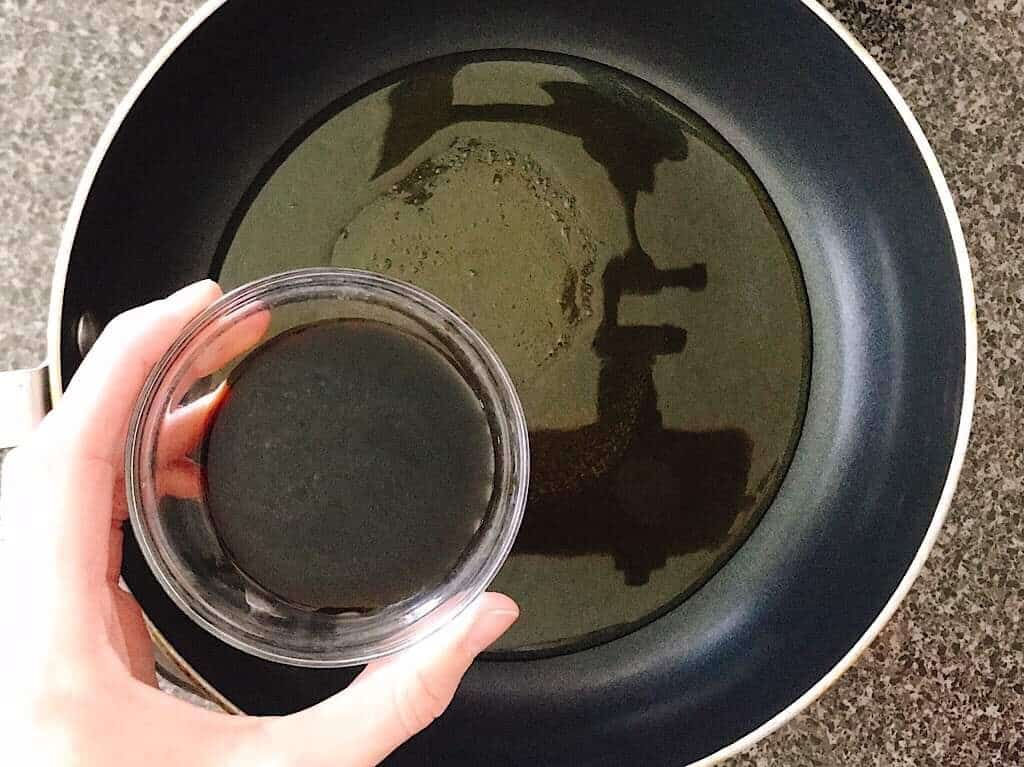A bowl of soy sauce being held over a saucepan.