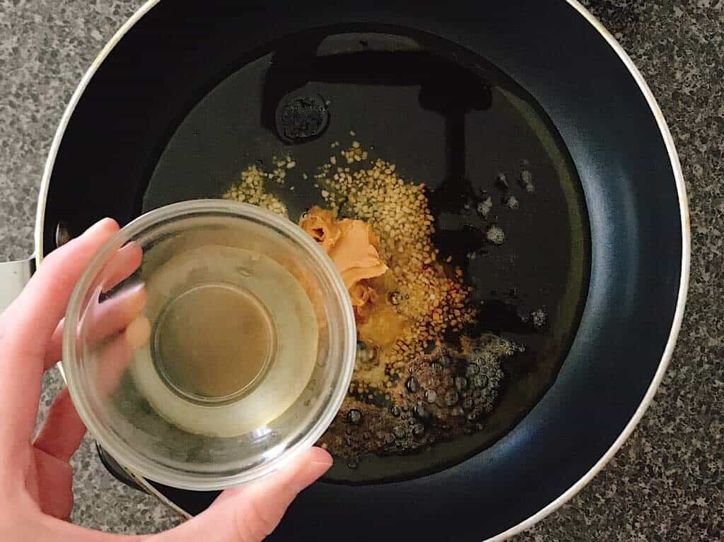 Rice vinegar in a small bowl about to be added to a saucepan.