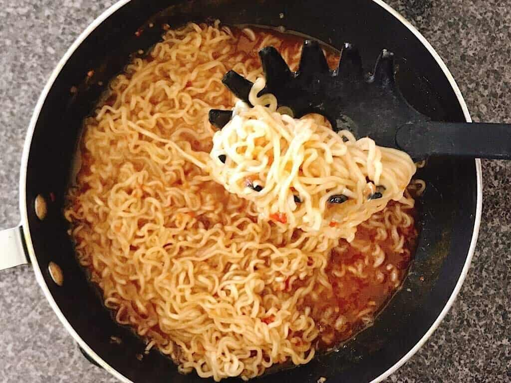 A pasta fork holding up noodles over a pan of sauce.