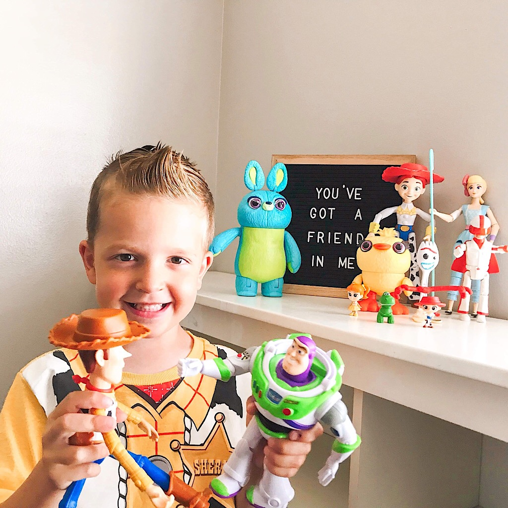 "A boy in a Woody shirt playing with Woody and Buzz Lightyear in front of more toys and a sign that says, ""You've got a Friend in Me."""