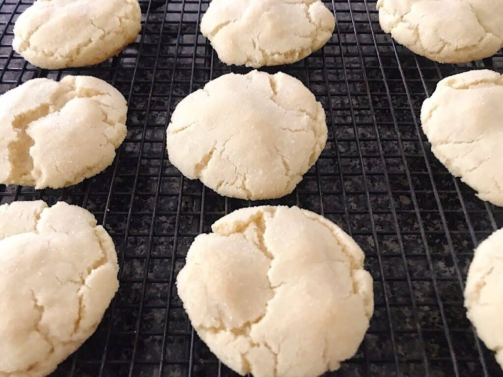 Sugar cookies lined up on a cooling rack.