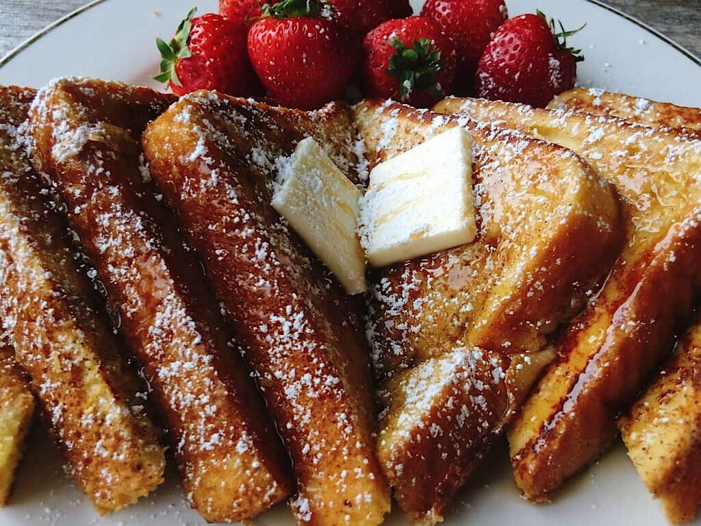 Slices of Perfect French Toast lined up with butter and strawberries.