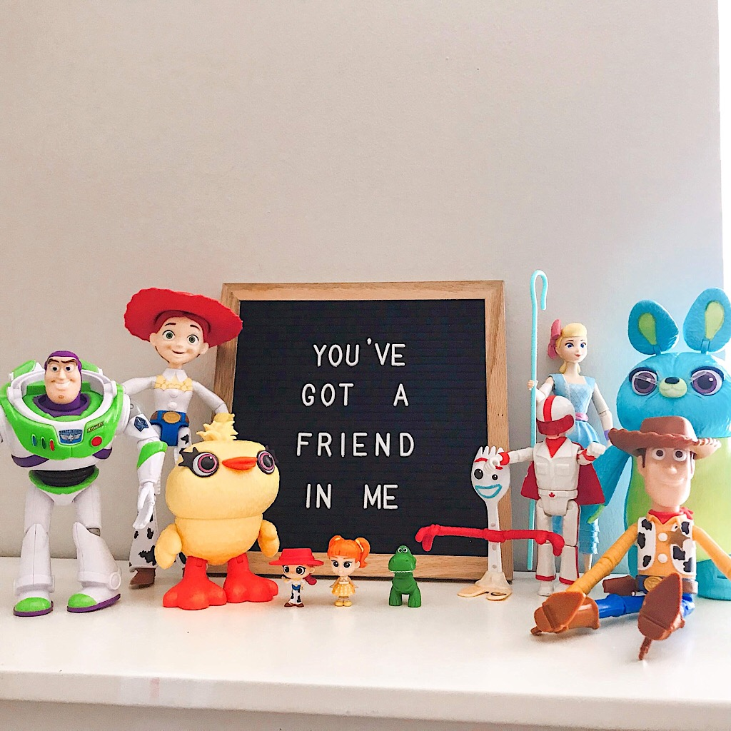 "The toys from Toy Story 4 lined up with a sign that says ""You've Got a Friend in Me"""