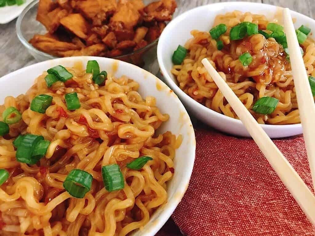 Two bowls of Spicy Thai Noodles and a bowl of Teriyaki chicken and chopsticks.
