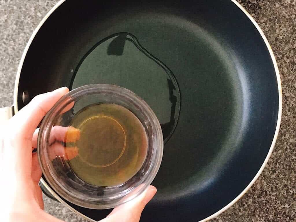 A bowl of sesame oil to be added to a pan.