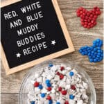 "A letter board with text ""Red, White and Blue Muddy Buddies Recipe"" with a bowl of Muddy Buddies."