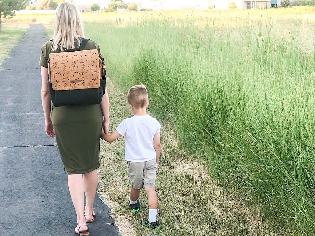 A woman with a backpack and her son walking on a path