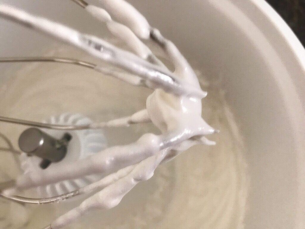 Whipped egg whites on a whisk to make crispy waffle batter.