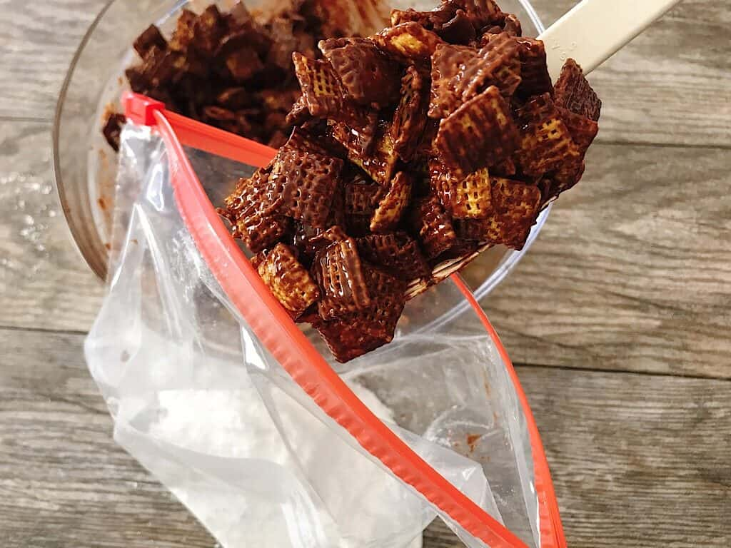 A spoon scooping A bag of chocolate covered Chex cereal in a ziplock bag with powdered sugar.