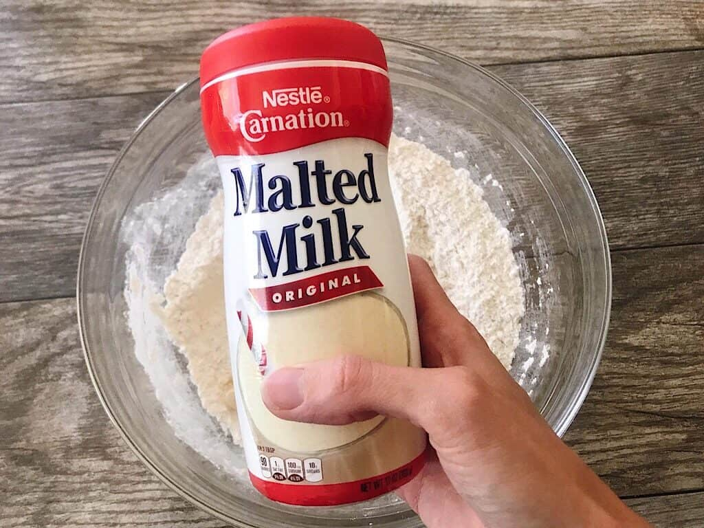 A container of Malted Milk over a bowl of flour.