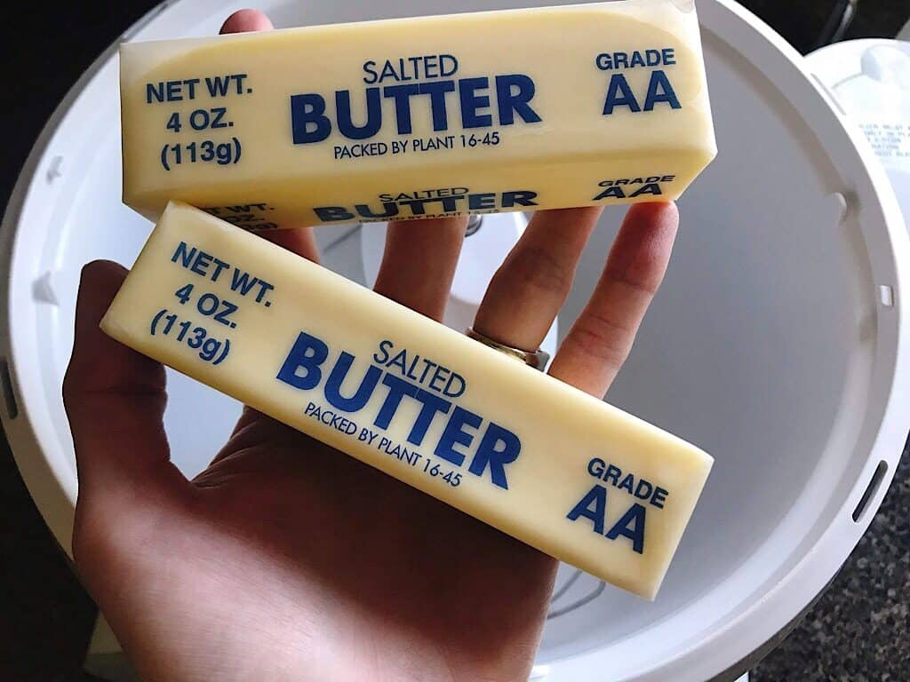 Two sticks of butter being held over a stand mixer to make cream cheese frosting
