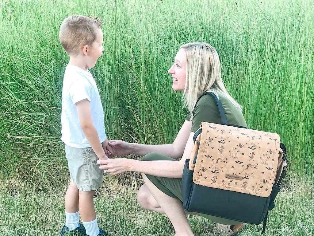 A boy and his mom in front of green grass.
