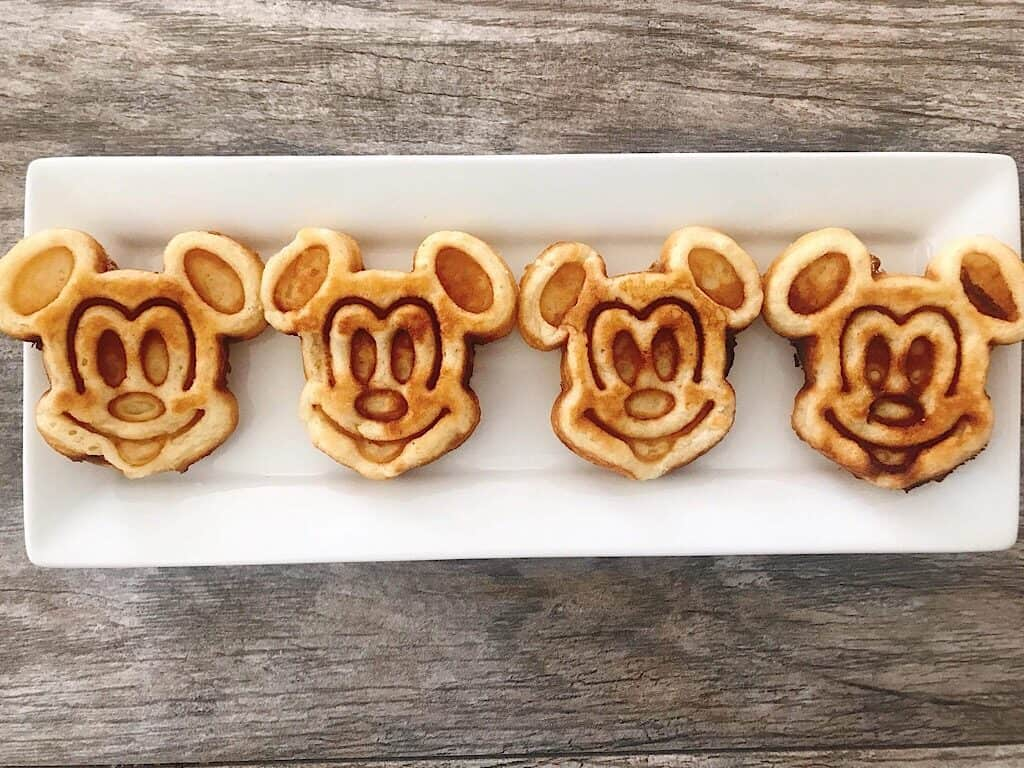 Crispy Mickey Mouse shaped waffles lined up on a white plate.