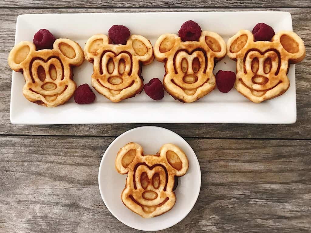 Crispy Mickey Mouse shaped waffles lined up on a white plate with raspberries.