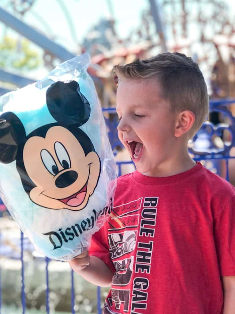 A boy excited to eat Mickey Mouse Cotton Candy at Disneyland