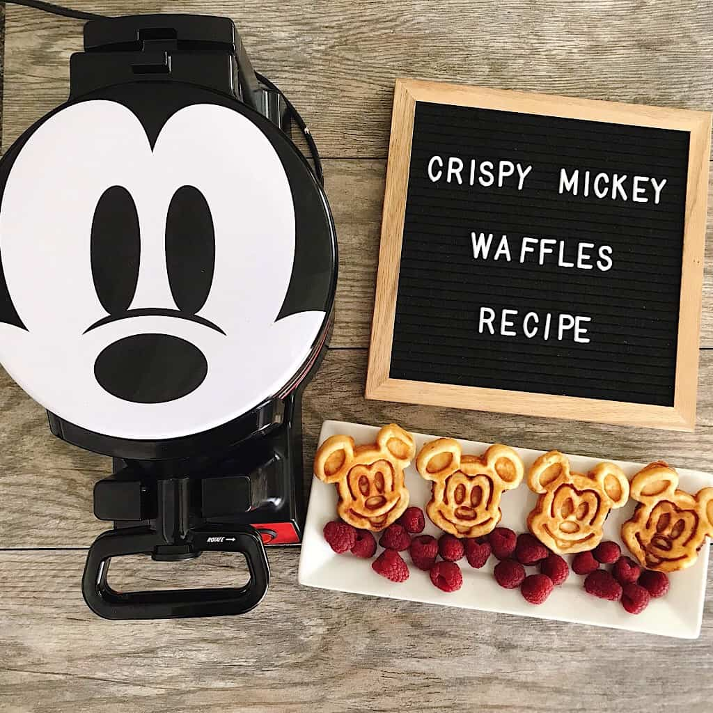 "A waffle iron with a Mickey Mouse face and a letter board that says ""crispy Mickey Waffles Recipe"" and a plate of Mickey Mouse shaped waffles on a white plate with raspberries."