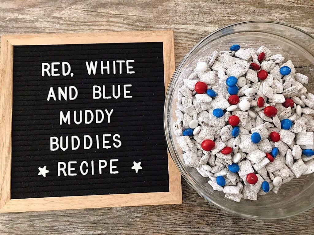 """A bowl of Muddy Buddies with Red, White, and Blue M&M's for the 4th of July and a Letter board sign that says """"Red White and Blue Muddy Buddies Recipe""""."""