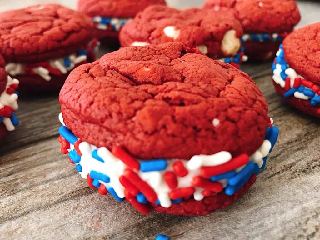 A red velvet cake mix sandwich cookie with red, white, and blue sprinkles.