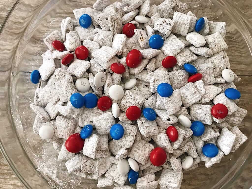 A bowl of Muddy Buddies with Red, White, and Blue M&M's for the 4th of July.