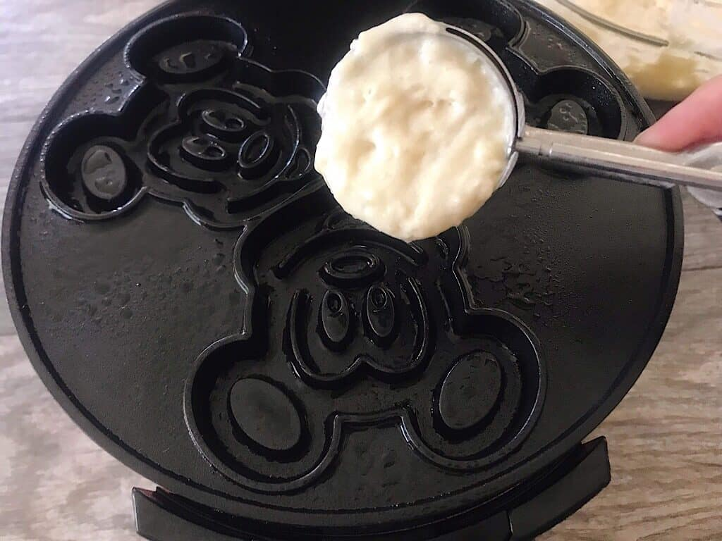 A scoop of crispy waffle batter over a Mickey waffle iron.