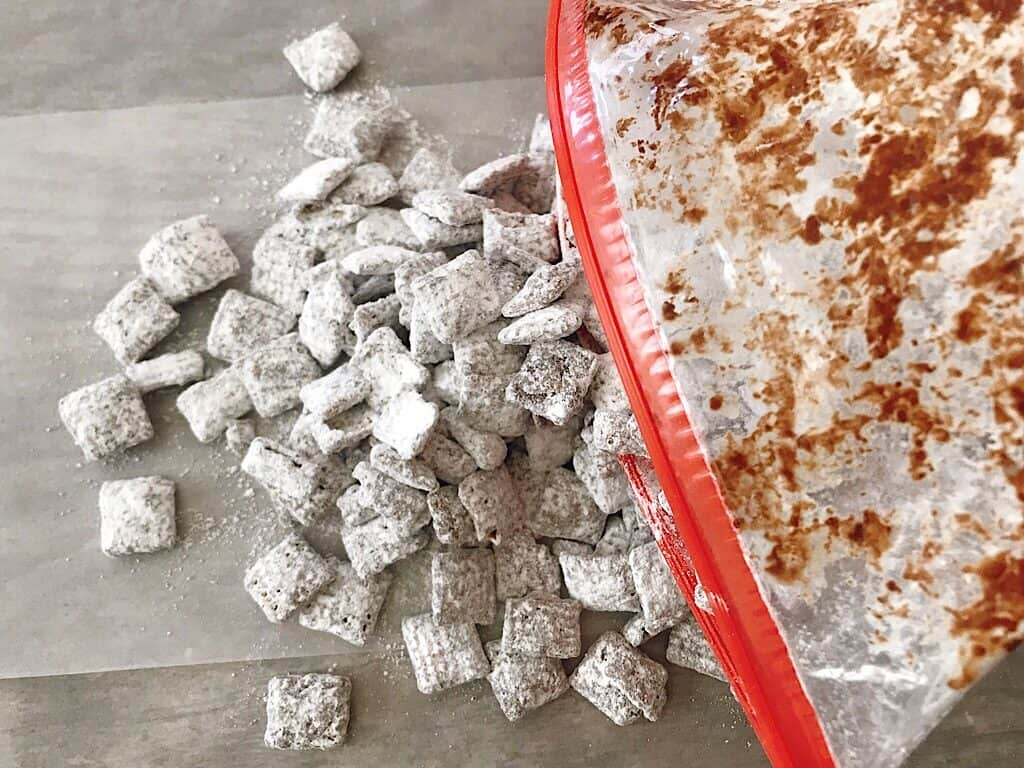 Muddy Buddies covered in powdered sugar being poured out of a ziplock bag.