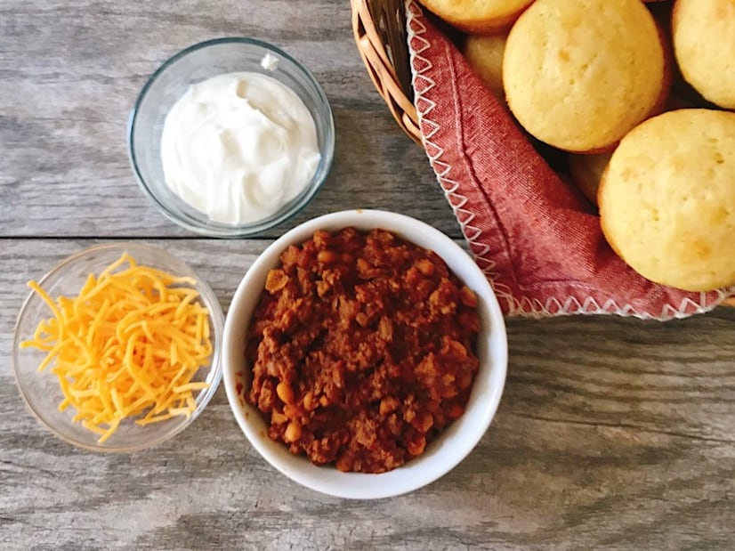A bowl of Buffalo Chicken Chili with cornbread muffins and toppings.