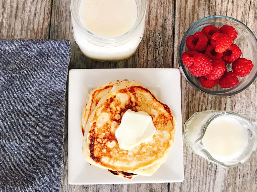 Buttermilk pancakes with syrup and raspberries