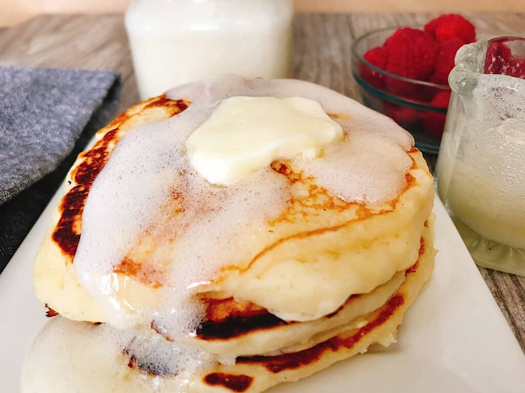 A plate of fluffy buttermilk pancakes covered with buttermilk syrup