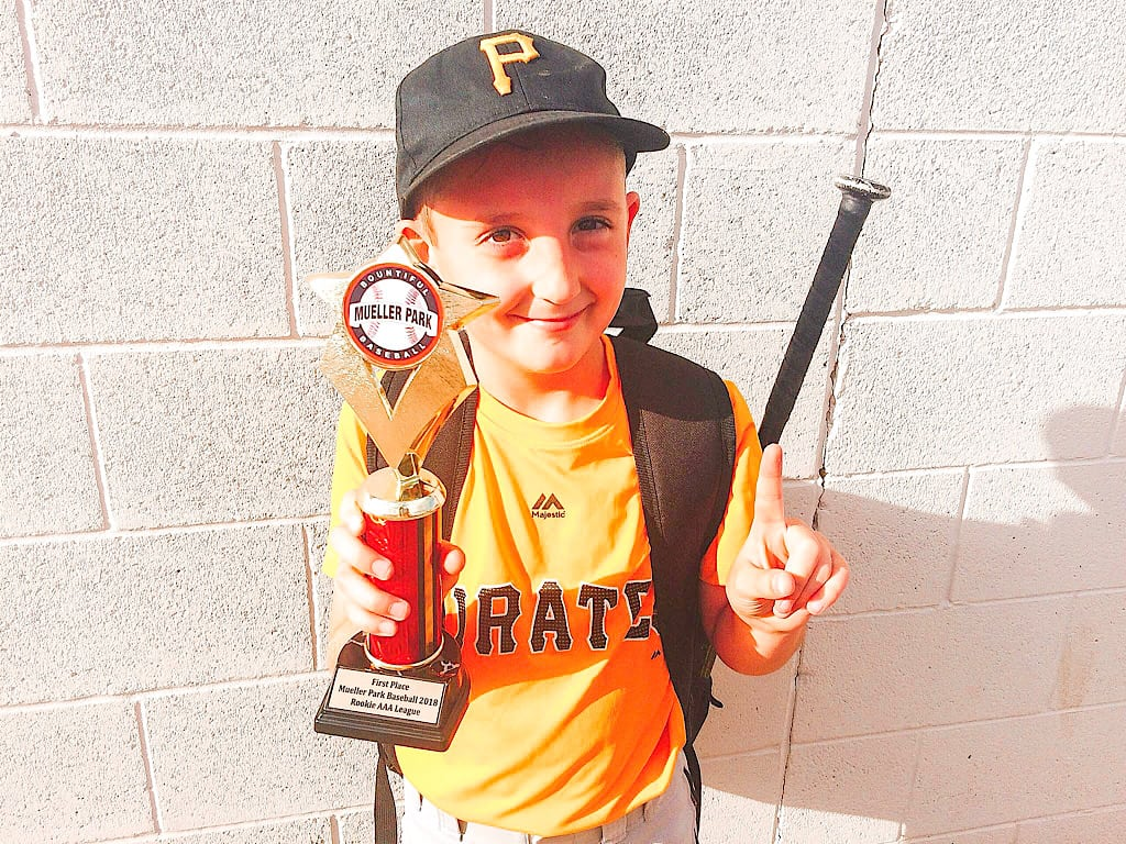 A young baseball player with a trophy