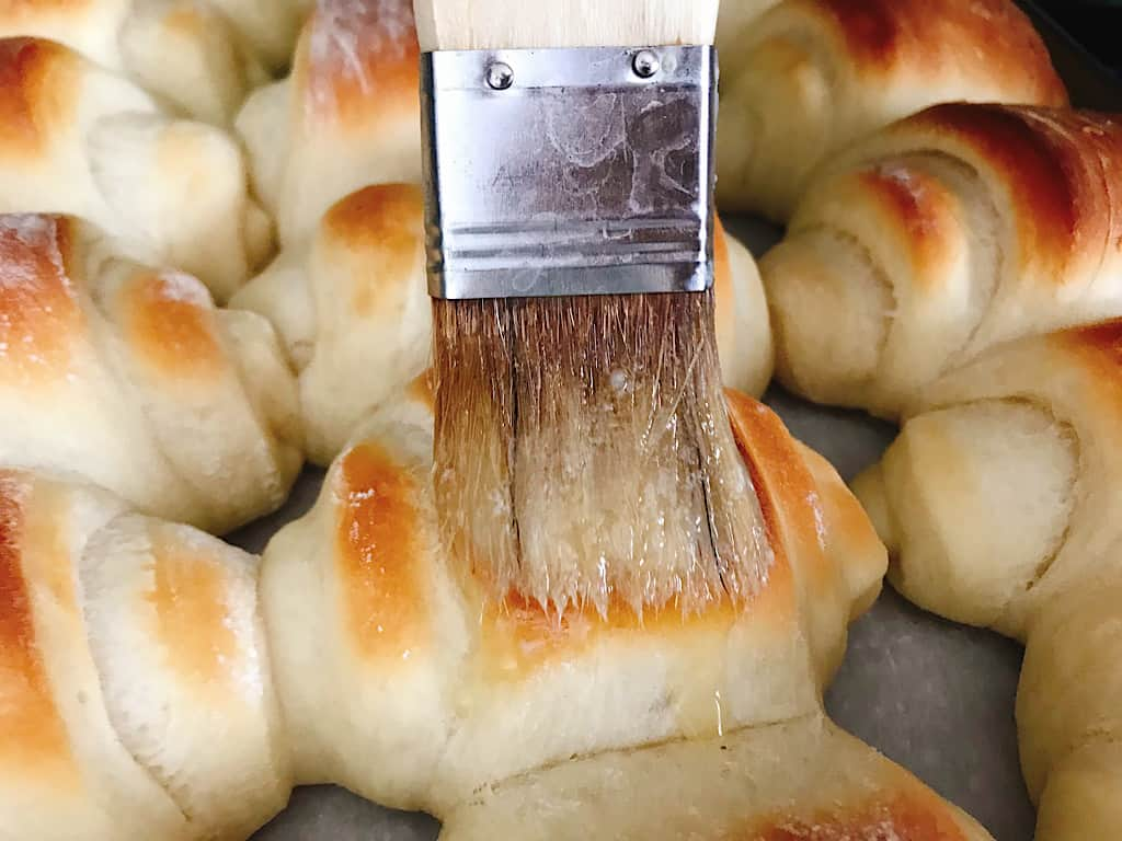 Melted butter brushed onto Lion House Rolls.
