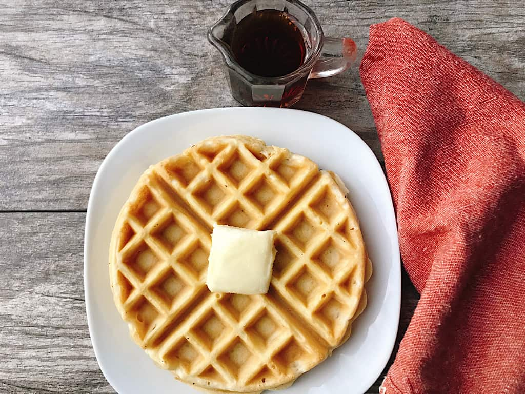 A waffle with butter and syrup