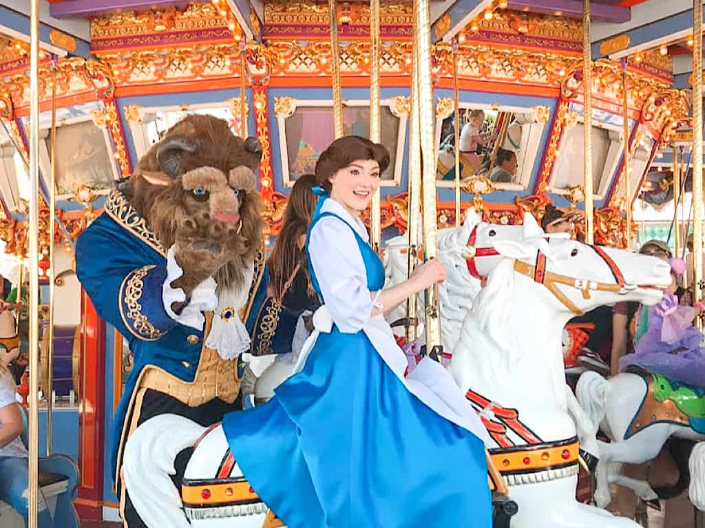 Belle and Beast riding a carousel at Disneyland