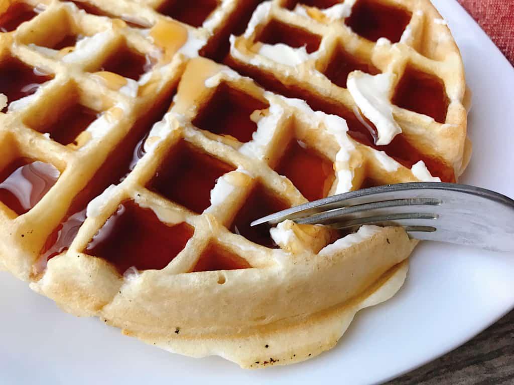 A fork cutting a waffle.