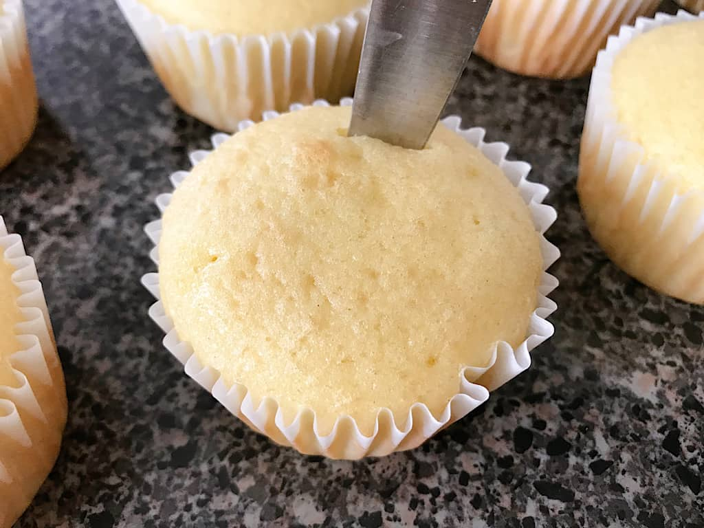 A knife cutting out the center of a vanilla cupcake to make strawberry cheesecake cupcakes