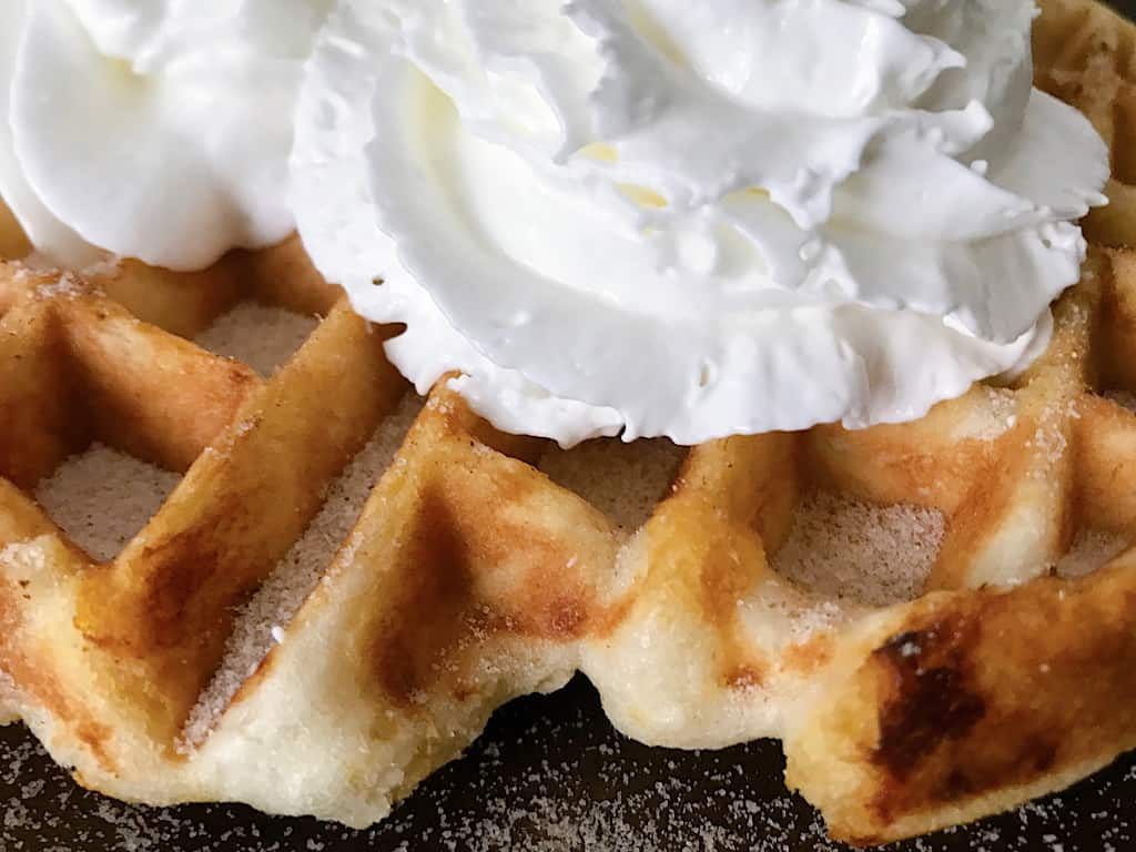 Close up picture of a funnel cake waffle and whipped cream